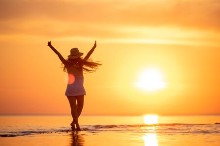 Young happy girl is standing or dancing at sunset beach with raised arms