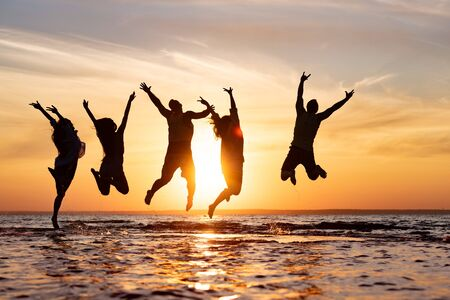 Five happy friends are having fun and jumping at sunset beach