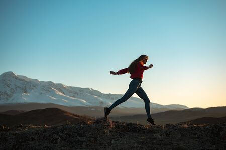 Slim sporty girl is walking in mountains at sunset time 免版税图像