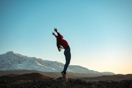 Young active girl is standing in winner pose in mountains at sunset or sunrise
