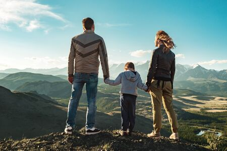 Family of father, mother and young child stands in mountains and looks at sunset