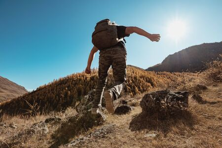 Active hiker with backpack runs and jums between rocks in mountains