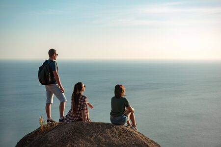 Three young friends enjoys sunset sea from mountain viewpoint