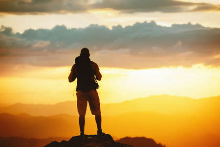 Unrecognized hiker stands with backpack on mountain top and enjoys sunset sky