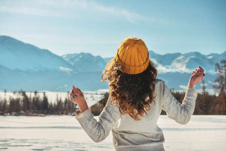 Attractive young girl walks in snowy mountains 스톡 콘텐츠