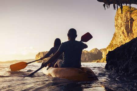 Active couple walks by kayak or canoe at sunset sea bay. Krabi province. Thailand