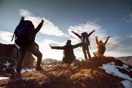 Four happy hikers stands in winner poses at mountain top at sunset time 스톡 콘텐츠