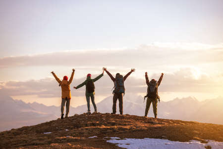 Four happy tourists stands with raised arms at mountain top against sunset mountains and sky