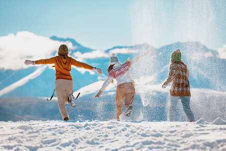 Three happy adult girls are having fun, runs and throwing snow in mountains. First snow concept
