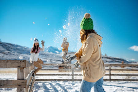 Happy adult girls are having fun and plays in snowballs at first snow in mountains Фото со стока