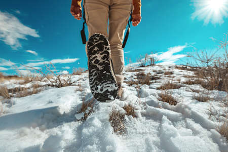 Lady hiker goes uphill by snowy surface. Closeup photo of woman legs