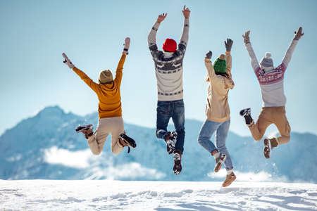 Friends celebrates beginning of winter in mountains, jumps and having fun Фото со стока