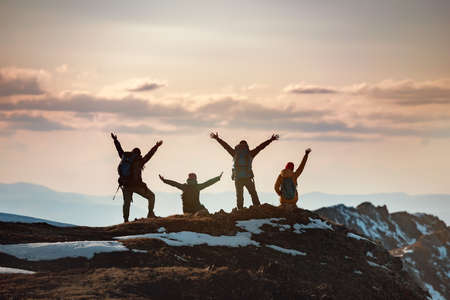 Group of happy hikers stands with raised arms in winner poses at mountain top and enjoys sunset Фото со стока