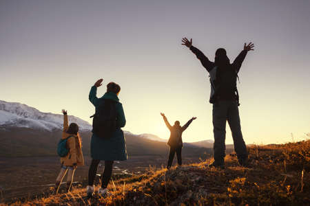 Four young hikers greetings with raised arms sunset in mountains