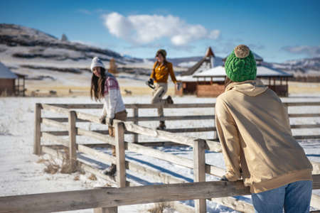 Three young girls friends are having fun at first snow in mountains. Winter vacations concept