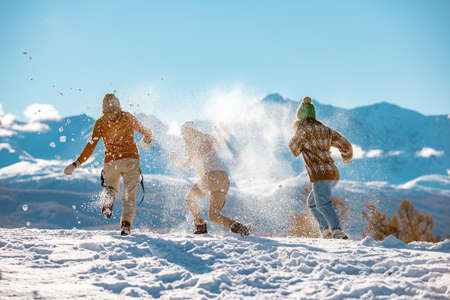 Three young happy girls friends are having fun in snow fight in mountains. First snow and winter vacations concept