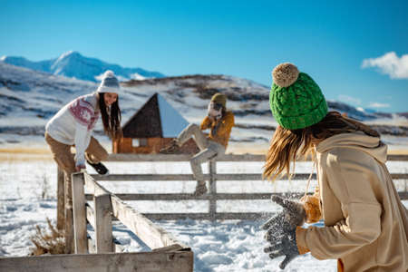 Three happy young girlfriends are having fun at wooden fence at wintertime outdoors in mountains. Winter vacations concept