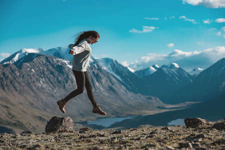 One slim sporty girl is having fun and jumps over the stone in high mountains. Active tourism concept