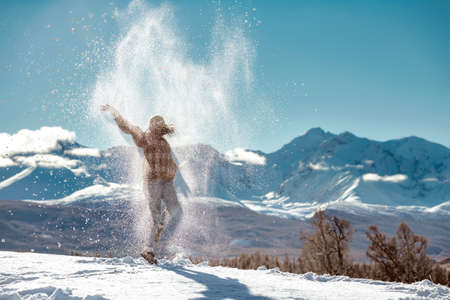 Happy girl is tossing powder snow and jumps in on background of mountains. Winter vacations concept