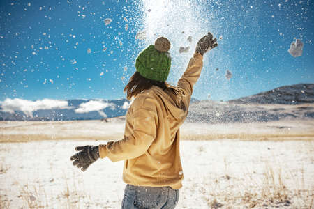 Happy girl is having fun and tossing snow in mountains. First snow concept Фото со стока