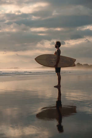 Athletic surfer stands with surfboard at serene evening beach. Bali island, Indonesia