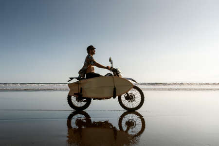 Real balinese surfer ride motorcycle with surfboard at ocean beach