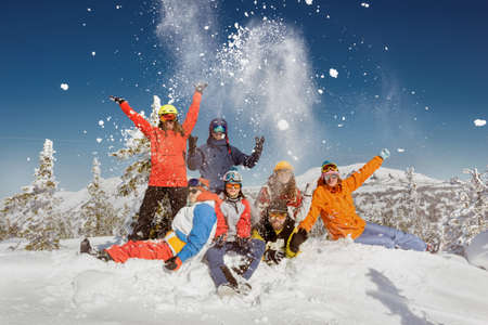 Group of young friends in colorful clothes are having fun and posing at the top of mountain. Winter ski and snowboarding vacations concept