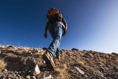 Unrecognizable male traveler or hiker goes uphill. Closeup photo from boots