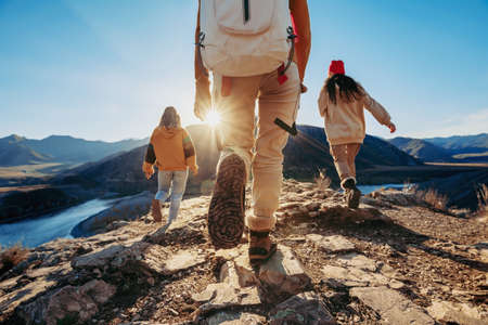 Three young tourists hikers walks against sunset mountains and river Фото со стока