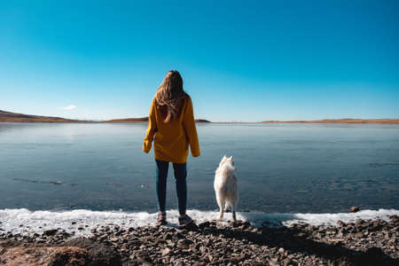 Young girl with white husky stands at frozen lake beach Фото со стока