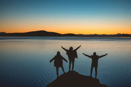 Silhouettes of three happy girls with raised arms stands against sunset lake and mountains