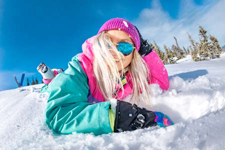 Happy girl snowboarder in colorful ski wear lies in powder snow and laughing. Ski resort concept