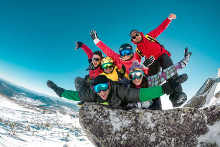 Group of happy friends tourists are having fun at ski resort. Ski and snowboard resort Sheregesh