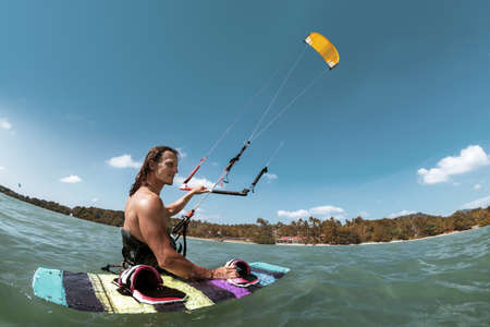 Athletic kite surfer stands in water with wakeboard