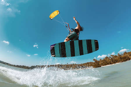 Athlete wakeboarder jumps with kite at sea bay. Phuket island, Thailand