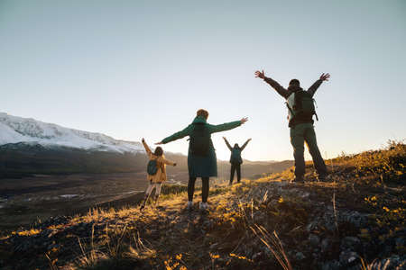 Happy hikers stands with raised arms and looking at sunset mountains 版權商用圖片