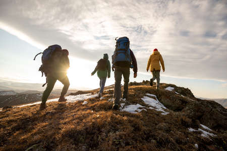 Group of four hikers with backpacks walks in mountains at sunset 版權商用圖片 - 163964987