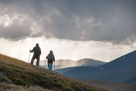 Two young hikers are standing on mountain slope against sunset rainy sky