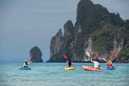 Four friends are walking by sea kayaks or canoes. Phi-Phi Don island, Krabi, Thailand