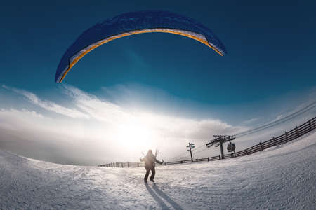 Lonely skydiver is taking off from mountain top at ski resort in sunset time. Sheregesh resort, Siberia, Russia Фото со стока