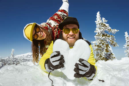 Romantic couple is having fun with heart of snow at ski resort. Winter vacations concept