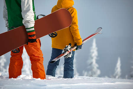 Couple of skier and snowboarder stands at mountain top. Unrecognized persons