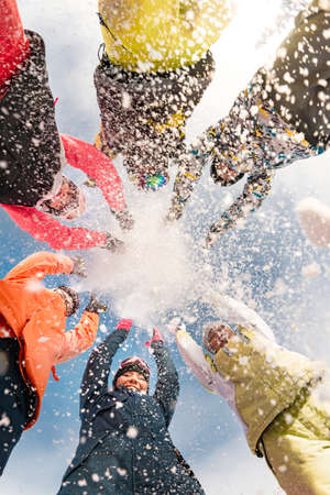 Group of happy friends at ski resort are having fun and throwing snow