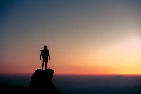 Silhouette of male traveler or hiker is standing at mountain top on background of sunset sky Фото со стока