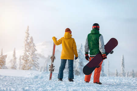 Female skier and male snowboarder are standing on background of snowcapped mountain at sunset time. Ski resort concept Фото со стока