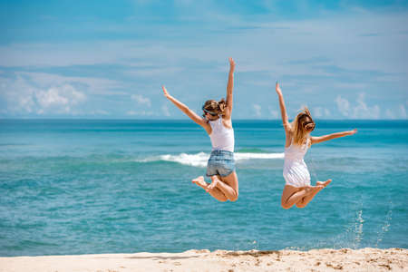 Two young girls are jumping on babkground of blue sea