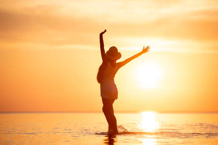 Ladys silhouette stands with raised arms at tranquil sunset beach