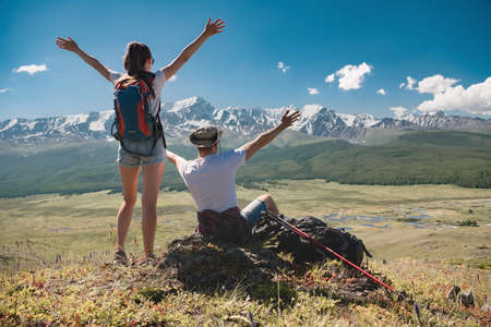 Happy couple of hikers stands with raised arms against mountains