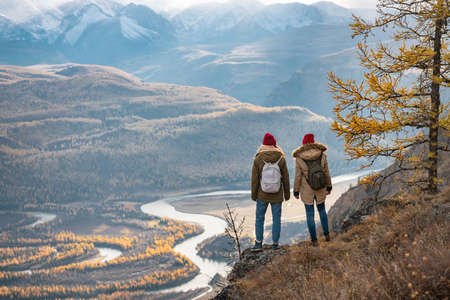 Two girls are standing at cliff and looks at mountains and river