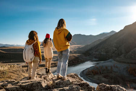 Three female hikers or tourists in sunset mountains